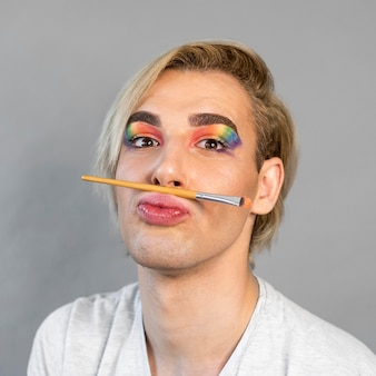 Homme portant des cosmétiques arc-en-ciel de maquillage
