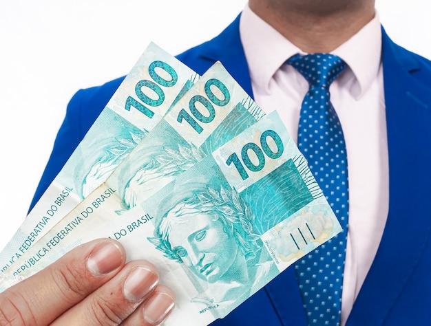 Un homme portant un costume bleu tenant un tas de billets royaux brésiliens fond blanc