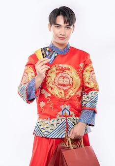 Un homme portant un costume cheongsam obtient beaucoup de choses en utilisant une carte de crédit au nouvel an chinois