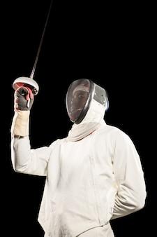 Homme portant un costume d'escrime pratiquant avec l'épée