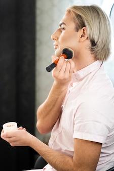 Homme portant du maquillage à l'aide de poudre