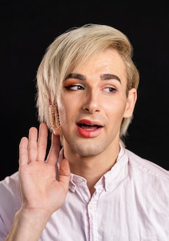 Homme portant du maquillage sur la moitié de son visage et regardant ailleurs