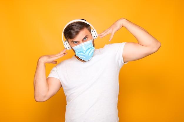 Un homme portant des écouteurs musicaux blancs se tient sur un fond jaune, portant un masque médical.