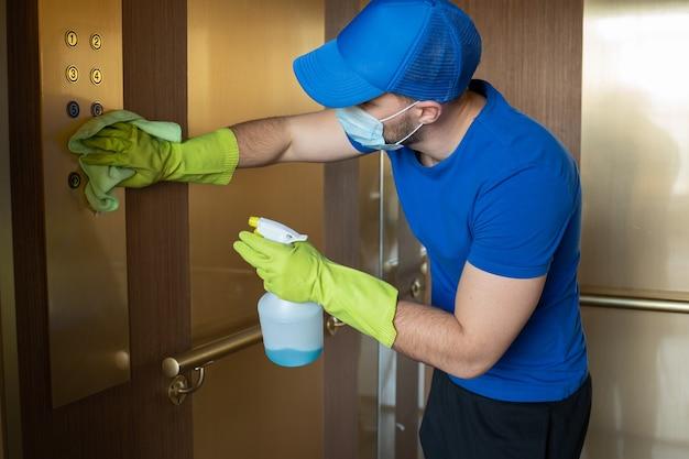 Homme portant des gants et un masque essuie les boutons et la main courante du personnel de nettoyage d'ascenseur désinfectant l'ascenseur pour éviter la contagion