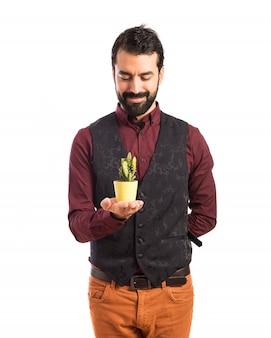 Homme Portant Un Gilet Tenant Un Cactus Photo gratuit