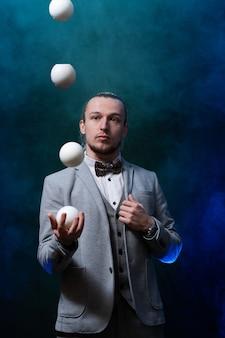 Homme portant une jonglerie noire avec des balles blanches