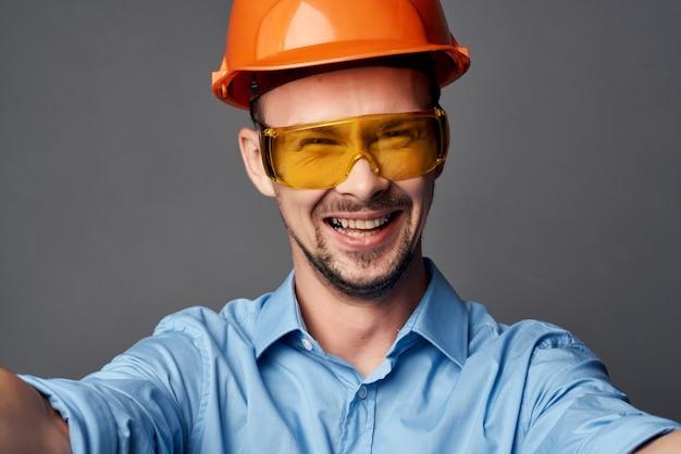 Homme portant des lunettes jaunes avec service de travail de sécurité de peinture orange
