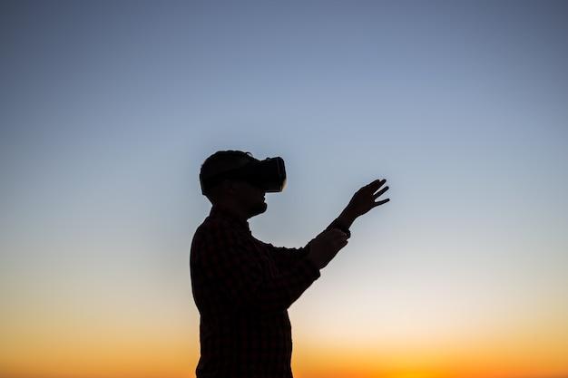 Homme portant des lunettes de réalité virtuelle au coucher du soleil