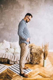 Un homme portant des lunettes représente une grossesse avec un ventre