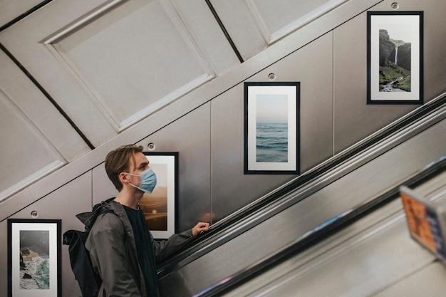 Homme portant un masque sur l'escalator souterrain