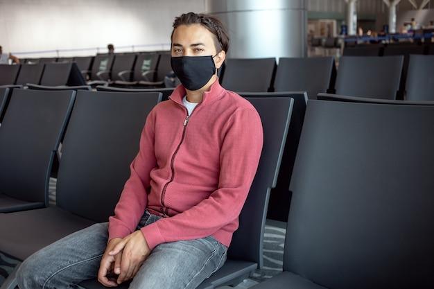 Homme portant un masque facial à l'aéroport. les thèmes voyagent dans la nouvelle norme, le coronavirus et la protection personnelle.