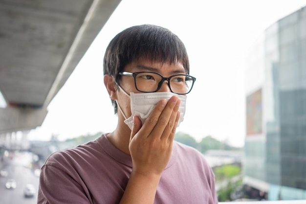 Un homme portant un masque facial protège le filtre contre la pollution de l'air (pm2.5)