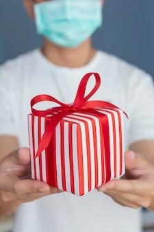 Homme portant un masque facial tenant une boîte cadeau rouge pour le nouvel an ou un cadeau de noël