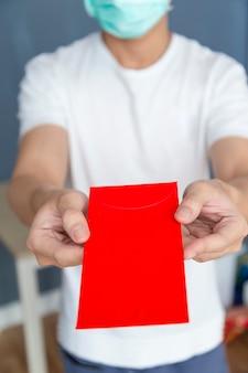 Homme portant un masque facial tenant une enveloppe rouge angpao pour cadeau nouvel an chinois