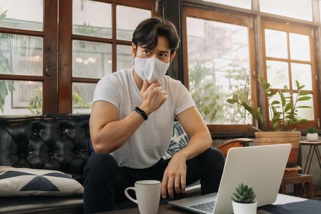 Un homme portant un masque facial travaille avec un ordinateur portable dans un café