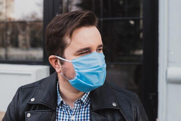 Homme portant un masque sur un fond de café fermé, coronavirus, maladie, infection, quarantaine, masque médical