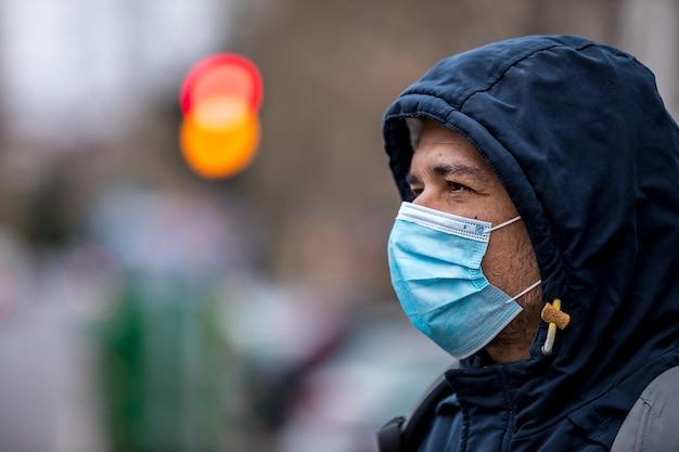 Homme portant un masque hygiénique facial à l'extérieur.