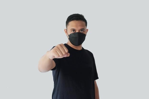 Homme portant un masque kf95 avec fisting à la main à l'avant