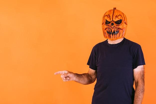 Homme portant un masque en latex de citrouille terrifiant avec un t-shirt bleu, pointant vers le côté gauche avec ses mains sur l'espace de copie, sur fond orange. halloween et jours des morts concept.