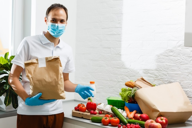 Un homme portant un masque médical démonte les sacs de nourriture à la maison. quarantaine. notion de santé. corona virus. commande de produits en ligne. livraison de produits à domicile. service de livraison