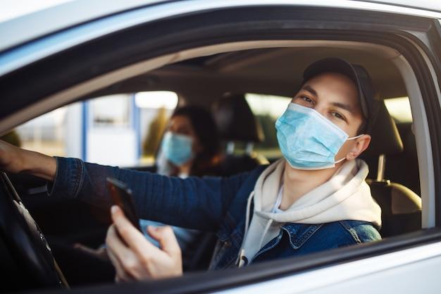 Un homme portant un masque médical tient un téléphone portable dans sa main tout en conduisant une voiture