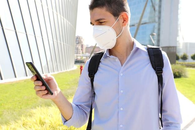Homme portant un masque de protection kn95 à l'aide de l'application smartphone