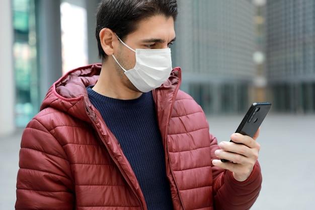 Homme portant un masque de protection lisant des nouvelles sur smartphone