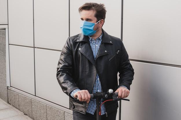 Homme portant un masque sur scooter électrique en contexte urbain