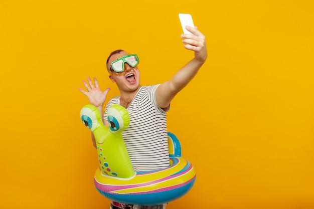 Homme portant un masque sous-marin chemise rayée tours de natation à la recherche dans le téléphone en prenant très émotionnellement selfie tout en souriant sur le concept de vacances de l'espace jaune