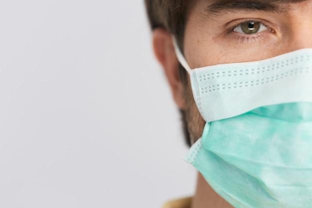Homme portant un masque stérile de protection regardant la caméra avec un œil tandis que le covid-19, copie espace, période d'isolement du coronavirus avec des masques aseptiques