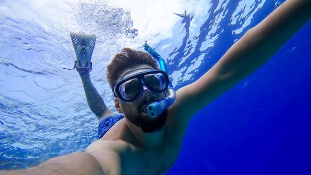 Un homme portant un masque et un tube respiratoire a plongé dans les profondeurs de la mer rouge et essaie de nager