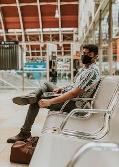 Homme portant un masque utilisant un ordinateur portable dans une gare dans la nouvelle normalité