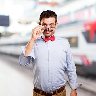 Homme portant un noeud papillon rouge. donnant sur des lunettes.