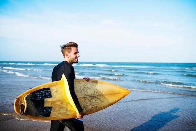 Un homme portant une planche de surf