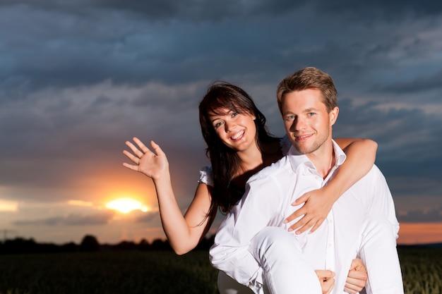 Homme portant sa femme avec le coucher de soleil en arrière-plan