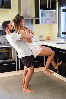 Homme portant sa femme heureuse dans la cuisine