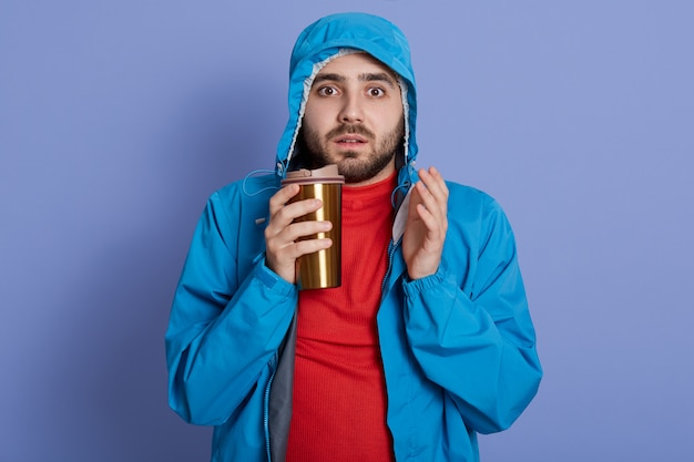 Homme portant une veste et une chemise rouge, boire du café contre le mur bleu, regardant directement la caméra avec une expression faciale étonnée