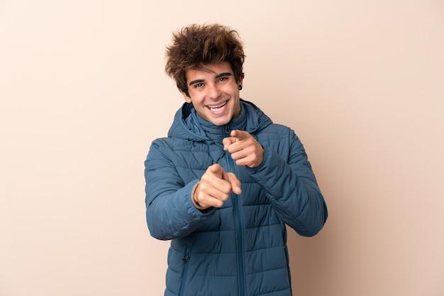 Homme portant une veste d'hiver sur le mur isolé pointe le doigt vers vous avec une expression confiante