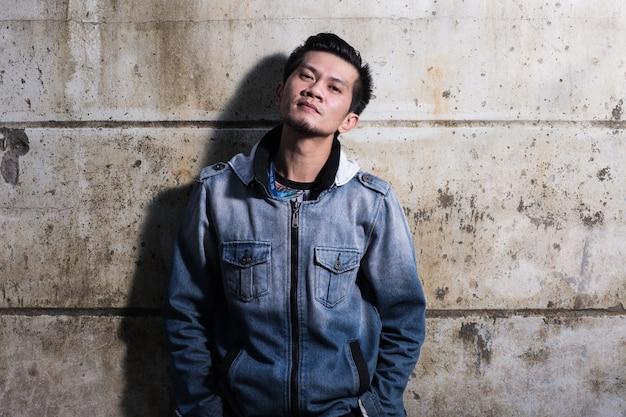 Un homme portant des vêtements en jeans se tient par terre devant le mur en ruines fissuré.
