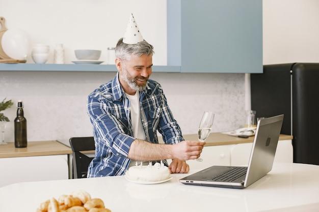 L'homme porte un chapeau de fête. l'homme garde un verre avec un champagne. l'homme a un appel via son ordinateur portable.
