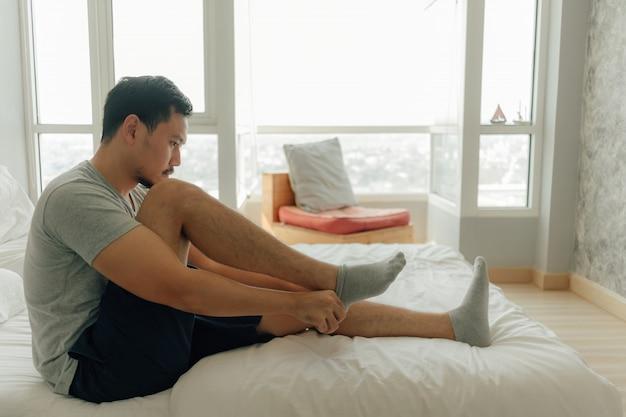 L'homme porte des chaussettes dans ses pieds dans la chambre