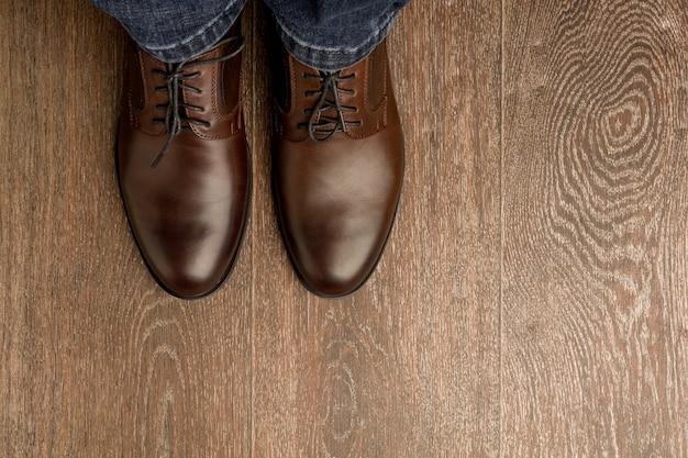 L'homme porte des chaussures classiques brunes sur de la farine de bois.