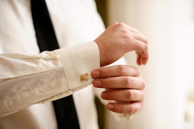 L'homme porte une chemise blanche et des boutons de manchette