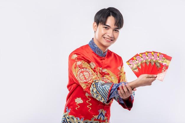 L'homme porte cheongsam est très chanceux d'obtenir de l'argent cadeau des parents dans la journée traditionnelle