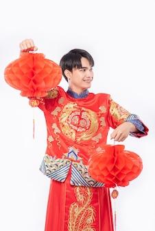 Un homme porte un costume de cheongsam pour décorer une lampe rouge dans sa boutique au nouvel an chinois