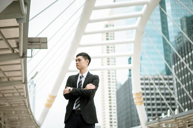 Un homme porte un costume noir, une chemise blanche et une cravate.