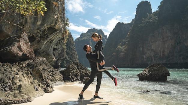 L'homme porte la femme dans ses bras sur la plage de phi phi, profitant de belles vacances d'été. concept de style de vie de vacances de voyage