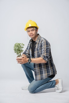 Un homme porte des gants orange et s'assoit pour tenir un pot de fleurs dans la maison.