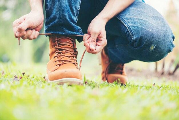 L'homme porte des jeans à genoux pour refaire ses lacets.