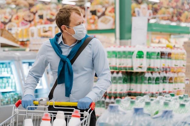 L'homme porte un masque médical jetable et des gants en caoutchouc, se tient au supermarché avec chariot, fait du shopping
